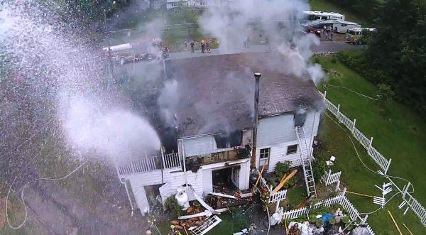 Brandweerman spuit drone uit de lucht